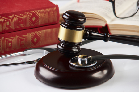 Law books with wooden judges gavel and medical stethoscope on white table in a courtroom or enforcement office, close-up. Medicine law concept. Stock Photo