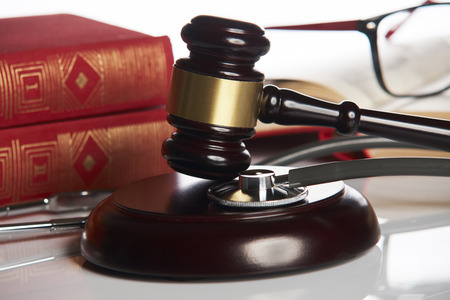 Medicine law concept. Law books with wooden judges gavel and medical stethoscope on white table in a courtroom or enforcement office, close-up. selective focus Stock Photo