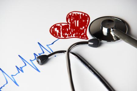Rastro del pulso del cardiograma con el concepto rojo del corazón y del estetoscopio médico para el examen médico cardiovascular en un fondo blanco con el espacio de la copia, visión superior. Concepto de salud