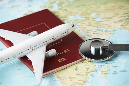 世界地図の背景に聴診器パスポート文書と飛行機を持つ医療旅行のコンセプト。 写真素材