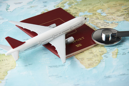 Medical travel concept with stethoscope passport document and airplane on world map background.