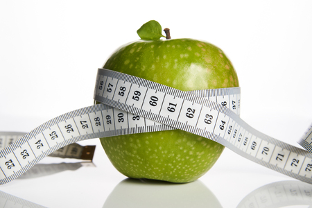 Green apple and measuring tape measured the meter on a white background, close-up. Healthy lifestyle, fitness and diet concept Banque d'images