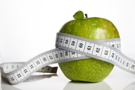 Pomme verte et ruban à mesurer ont mesuré le mètre sur un fond blanc, gros plan. Concept de mode de vie sain, de remise en forme et de régime