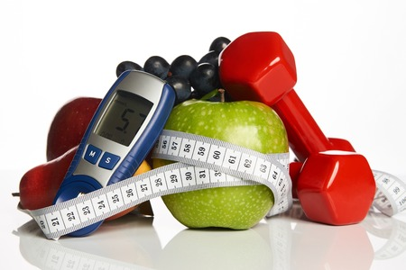 Blood sugar control glucometer for glucose level with healthy organic food and dumbbells with measuring tape on a white background. Healthy lifestyle, detox, weight loss and Diabetes concept Foto de archivo