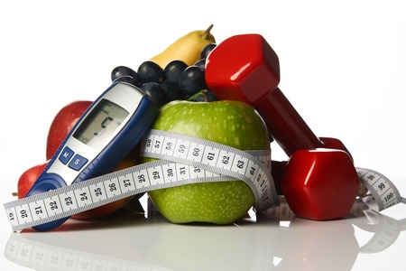 Blood sugar control glucometer for glucose level with healthy organic food and dumbbells with measuring tape on a white background. Healthy lifestyle, detox, weight loss and Diabetes concept Stock Photo
