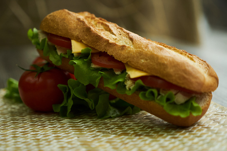 Baguette sandwich with turkey breast, cheese, lettuce, tomatoes and onion on a cutting board. Long subway sandwich on a rustic background, close-up Stock Photo