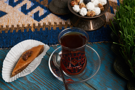 Pakhlava or baklava with glass of black tea and sugar sweet snacks in silver bowl on wooden rustic table with wheat grass semeni and blue carpet. Novruz holiday Stock Photo