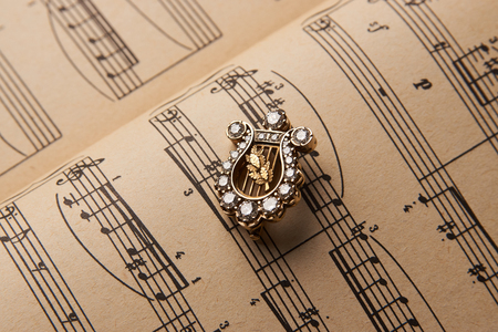 Diamond brooch in shape of harp musical instrument, close-up. Luxury female jewelry