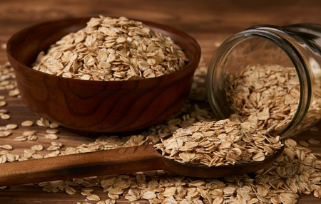 Oatmeal or oat flakes on old wooden table background, close-up. Healthy vegetarian diet food and agriculture concept Stok Fotoğraf