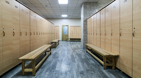 Wooden lockers with a wood bench in a locker room with doors closed. Locker room interior in modern fitness gym Standard-Bild