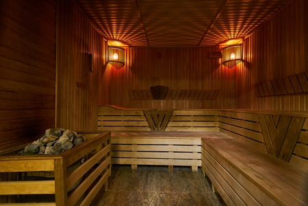 Wooden sauna interior. Relax in a hot small Finnish wooden sauna room in SPA centre Фото со стока