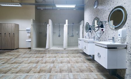 Public shower interior with everal showers, toilet sink and lockers in locker room in luxury fitness spa centre