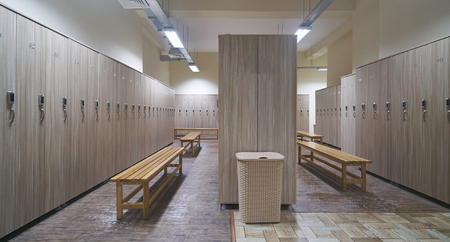 Locker room with wood benches and wooden lockers in the gym