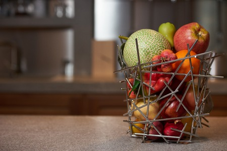 Fresh tropical fruits in abstract vase on kitchen counter table in luxury modern kitchen interior. Healthy vegetarian diet food and detox concept. Close-up, copy space