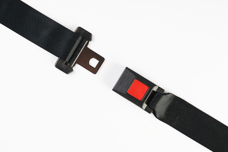 Black Open Seat Belt Isolated on White Background, close-up. Safety concept