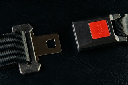 Opened seat belt on black leather background, close-up. Safety concept Stok Fotoğraf