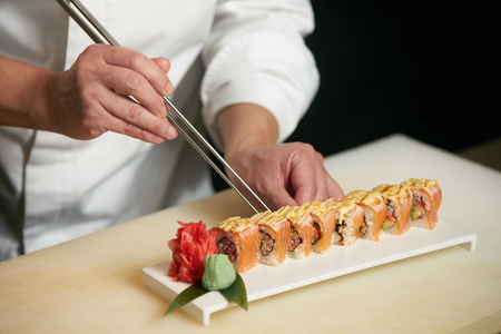 Chef prepares sushi with torch burner. Classic Japanese sushi food served on a stone plate