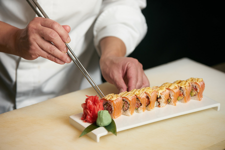 Male chef cooks preparing sushi in the restaurant kitchen. Chef cooking Classic Japanese sushi, served on a stone plate Stock Photo