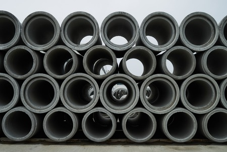 Stacked cement pipes at concrete factory, outdoors warehouse . Industrial production of cement products. Industry manufacturing concept