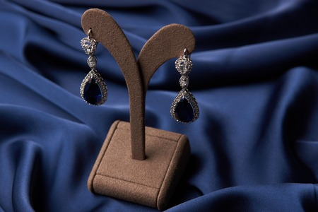 Close-up of a Beautiful platinum earrings and bracelet. Luxury women jewelry with diamonds and sapphire on blue silk background, selective focus