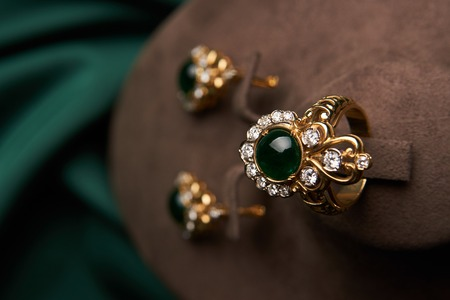 Beautiful Golden ring and pair of earrings with green Emerald and Diamonds gemstones on a green satin background. Luxury female jewelry, close-up. Selective focus Stock Photo