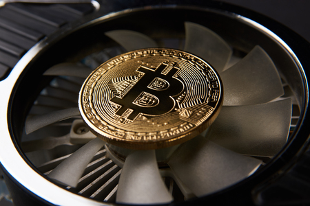 Bitcoin and video card, close-up. Cryptocurrency mining concept with golden bitcoins. Bitcoin mining farm device