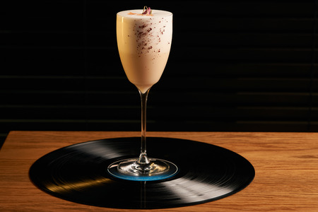 Classical Lucy cocktail on vinyl tray background. Cocktail with Gin, Yogurt, liqueur, Lychee puree, Cardamom syrup, egg white, Lemon juice. Sweet cocktail with spicy taste, close-up