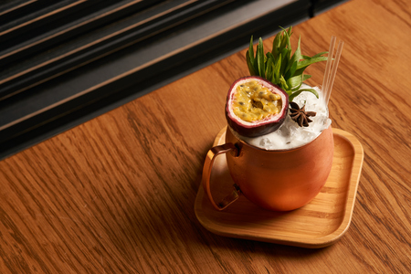 Spicy Mule cocktail on bar table. Alcoholic beverage drink with Rum angostura, reserve rum, dry orange passionfruit ,pure, pineapple pure, spice syrup ingredients, close-up Stock Photo