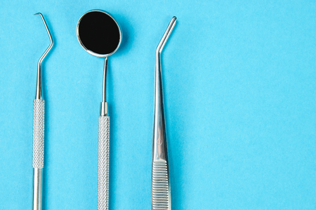 Professional Dentist tools on blue background with copy space. Dentist mirror, forceps curved, explorer curved, dental explorer angular and explorer curved with chip in dental office. Hygiene concept Stock Photo