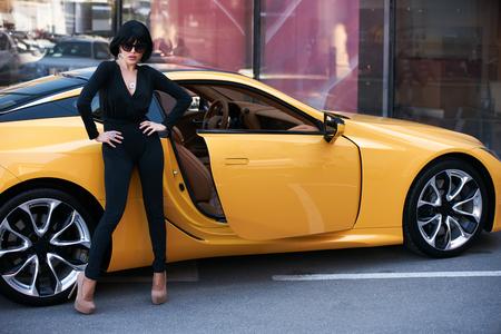 Belle femme brune avec une voiture de sport jaune. Jeune femme aux cheveux noirs en body noir et lunettes de soleil posant près de supercar