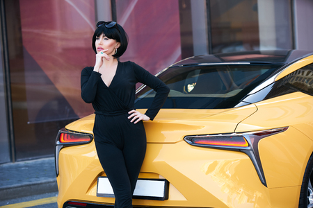 Young woman with dark hair in black bodysuit and sunglasses posing near supercar. Portrait of a Beautiful brunette woman with yellow sport car