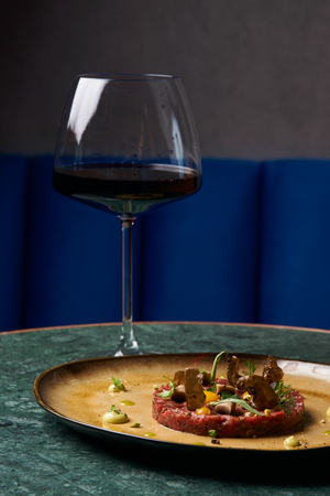 Beef tartare Steak with egg yolk, pistachios, truffle oil, green mayonnaise on porcelain plate and glass of red wine on restaurant table. Classic tartare meat with ingredients. Luxury food
