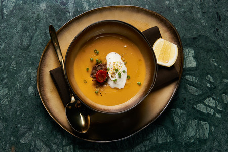 Lentil cream soup with baked lamb, cream fresh and spearmint. Delicious healthy soup food in bowl plate on table background, close-up, top view Stok Fotoğraf