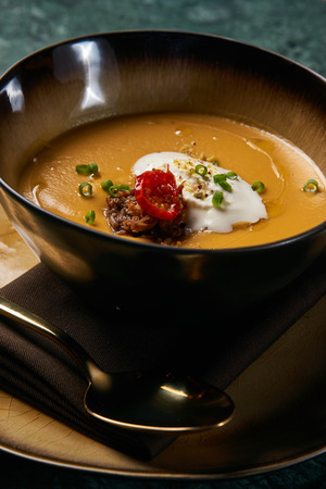Hot Lentil cream soup with baked lamb, cream fresh and spearmint. Delicious healthy soup food in bowl plate on table background, close-up, top view