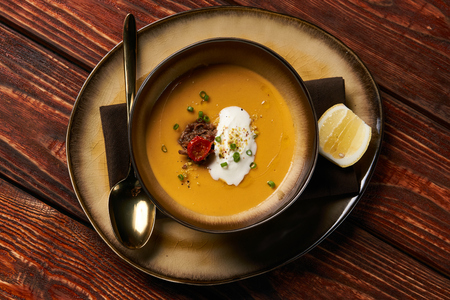 Traditional Lentil cream soup with baked lamb, cream fresh and spearmint. Delicious healthy soup food in bowl plate on table background, close-up, top view, copy space Stok Fotoğraf