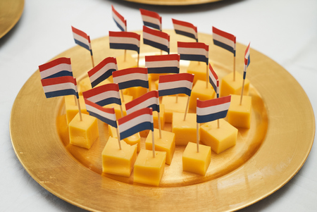 Dutch cheese cubes with flags. Gouda cheese snack with a dutch flag on a white table background, close-up Stockfoto