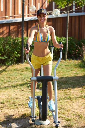 Young woman exercising with exercise equipment in the public park. Strong girl in training suit working out at outdoor gym. Sport fitness and healthy lifestyle concept Stock Photo