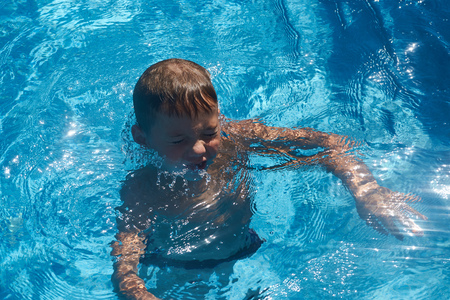 Drowning kid into swimming pool water. Young boy sinking into the sea.