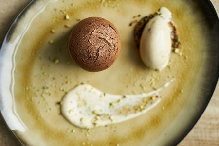 Dessert Fondant cake and pistachio ice cream with English cream, pistachio crumble and sauce bailies Banque d'images