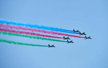 Modern military jet fighter airplanes flying in blue sky. Fighter jets fly together with colorful smoke