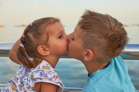 Kleines Mädchen, das kleinen Jungen draußen küsst, Nahaufnahme. Bruder und Schwester spielen und küssen sich