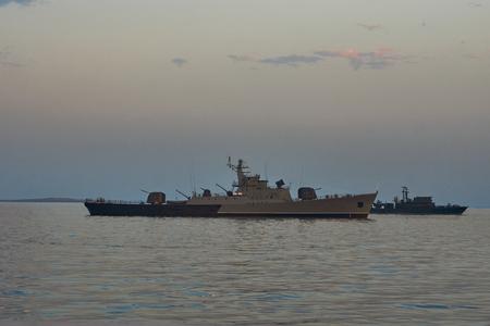 Military Battleships in a sea bay at sunset time. Modern warship sailing in still water. Coast Guard Ships guarding ocean