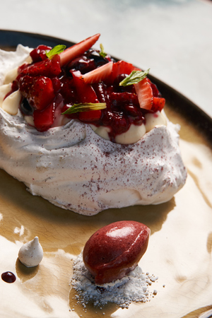 Meringue, Pavlova cake with berries and ice cream, close-up