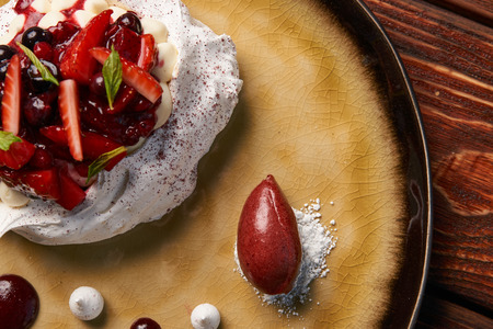 Tradicional Pavlova cake and ice cream served on plate, close-up Stock Photo