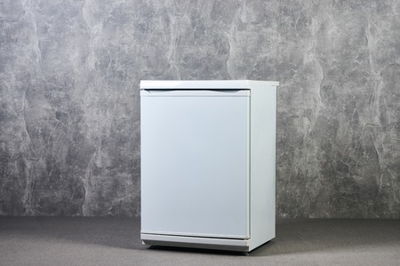 White Empty mini fridge or mini bar against gray textured wall background. International Exhibition furniture elements in large warehouse interior.