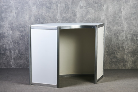 White showcase stand against gray textured wall background. International Exhibition furniture elements in large warehouse interior. Stock fotó