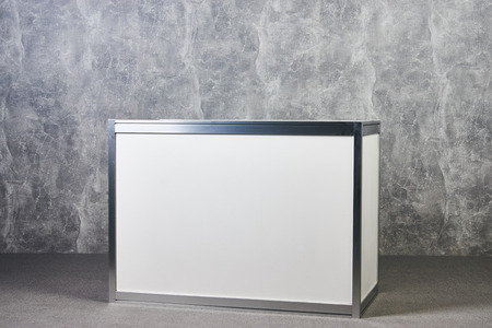 White glass showcase stand against gray textured wall background. International Exhibition furniture elements in large warehouse interior.