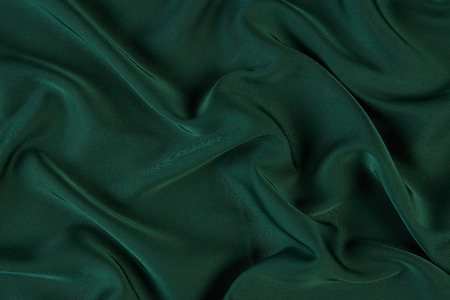 Green silk fabric background, view from above. Smooth elegant green silk or satin luxury cloth texture can use as abstract background with copy space.