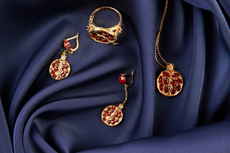 Rubies ring, necklace and earrings on blue silk background with copy space. Beautiful precious womens gold jewelry, close-up.