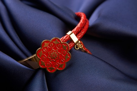 Pair of two Jewelery bijouterie rings with red leather on blue silk background with copy space, Beautiful precious womens jewelry, close-up